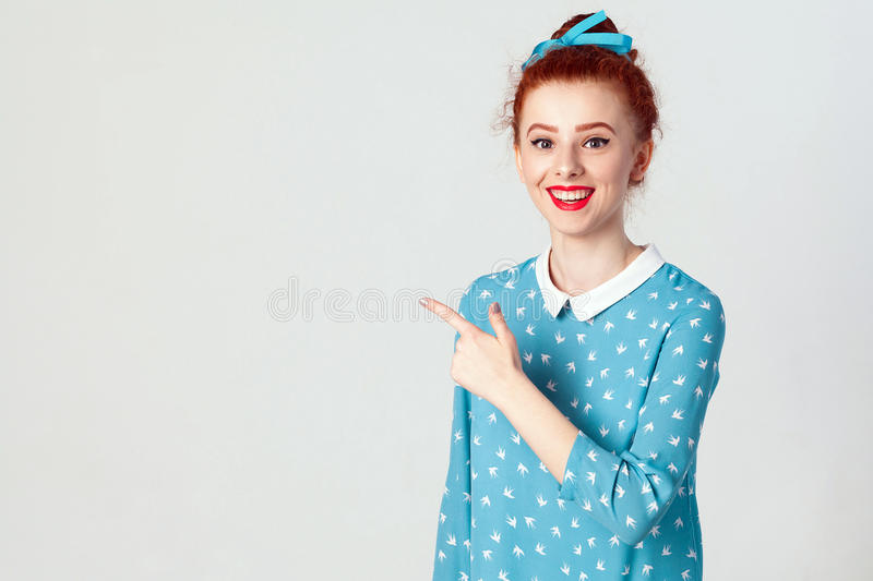 Young redhead caucasian girl with hair bun pointing her index finger away, indicating copy space on white blank wall for your cont royalty free stock image