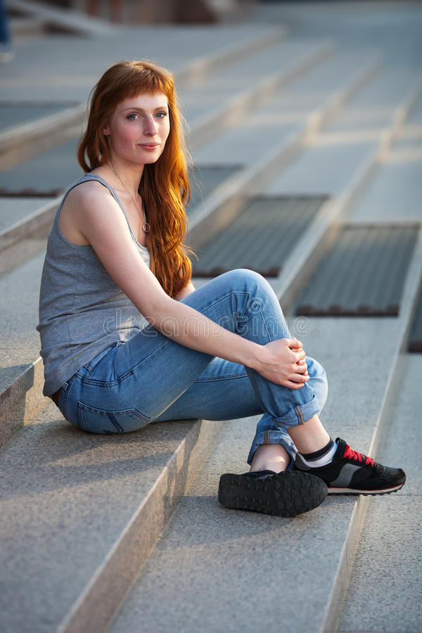 Young redhead caucasian woman in grey shirt blue jeans black sneakers sitting on stairs outdoor portrait royalty free stock photo