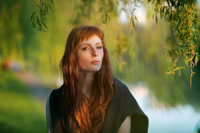 Young redhead caucasian woman serious face outdoor portrait in film retro colors stock photos