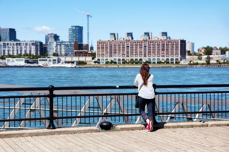 Redhead female watching the scenery of Montreal city and the Saint Lawrence river on a sunny summer day in Quebec, Canada. Young redhead female watching the stock image