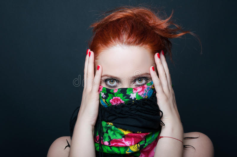Young redhead girl with floral scarf over mouth stock images