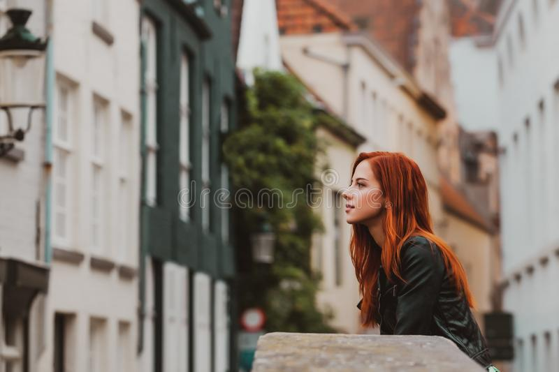Young redhead girl rest on the street in Brugge stock photo