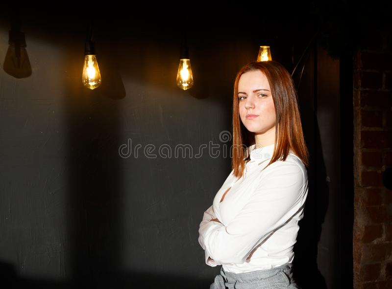 Young redhead girl in stylish clothes on wall background in loft style, solar light, place for copyspace royalty free stock photos