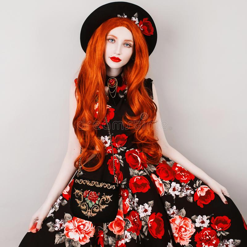 Young redhead girl with very long wavy hair in a dress with ornaments of roses on a gray background. Beautiful girl with pale skin, red lips and blue eyes in a stock images