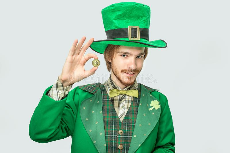 Young redhead man hold golden 100 coin and look on camera. He quite happy. Guy wear green saint Patrick`s suit. royalty free stock photo