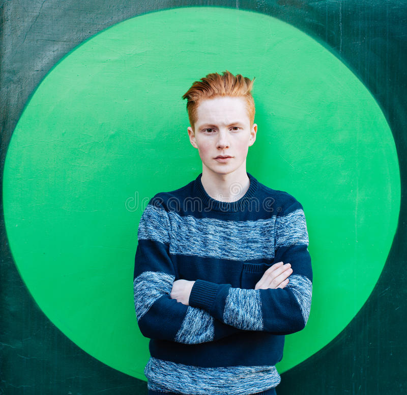 Young redhead man in a sweater and jeans standing next to green wall with folded arms. Irish stock images