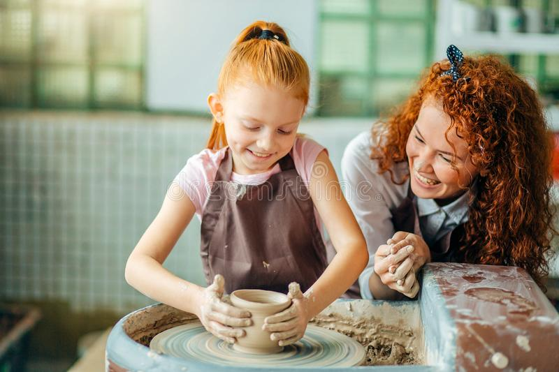 Redhead mother and her child daughter moulding with clay on pottery wheel royalty free stock image