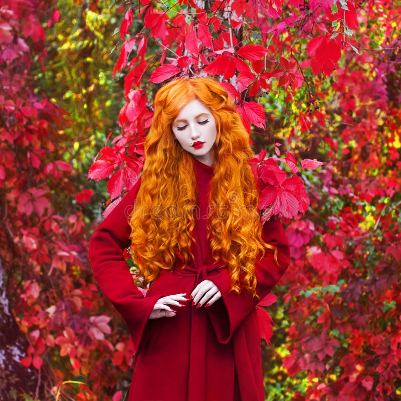 Young redhead girl with very long curly hair in a red coat on a bright autumn background. A beautiful model with pale skin. Red lips and closed eyes. Orange royalty free stock photo
