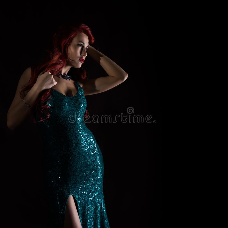 Young redhead woman in blue elegant dress poses in a dark. free space for your text stock images