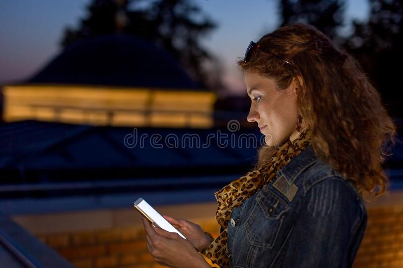 Young redhead urban woman looking into cell phone at evening stock photos
