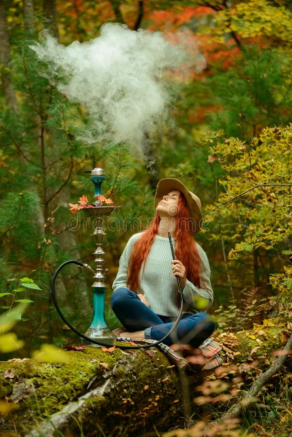 Young redhead woman smoking Hookah in forest. Young redhead woman in hat smoking Hookah in forest stock photography