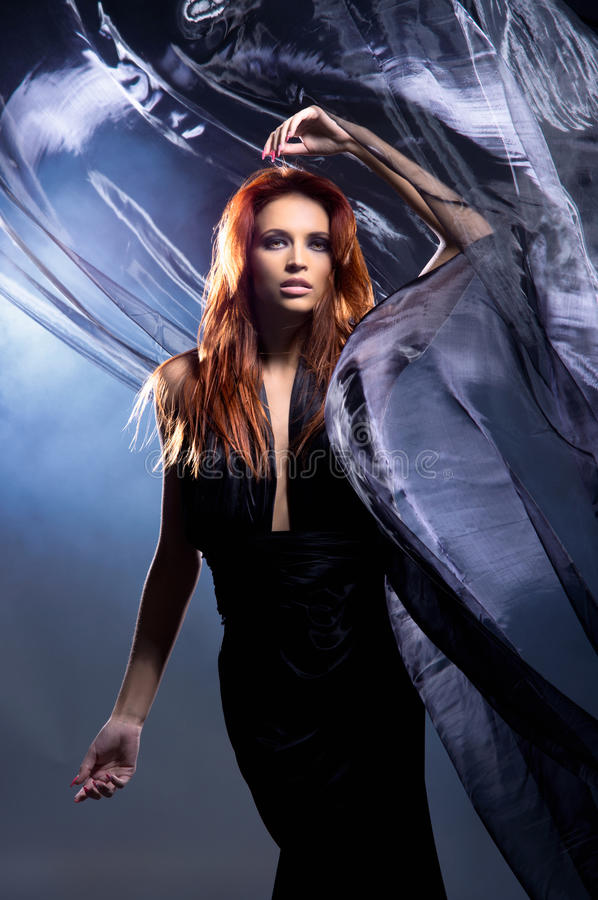A young redhead woman posing in a mystique dress royalty free stock photo