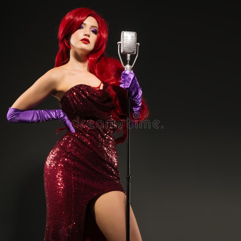 Young redhead woman retro style singer. Vintage microphone and dark background stock photos