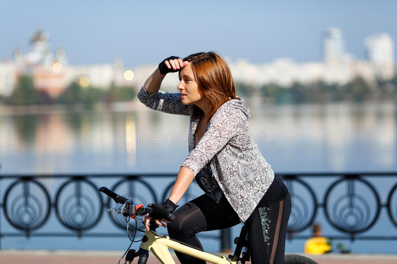 Young redhead woman riding a bike on embankment. Active people outdoors. Sport lifestyle. Young redhead woman riding a bike on embankment. Active people royalty free stock image
