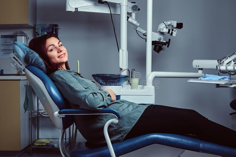 Young woman sitting in a chair in a dentist office. royalty free stock images