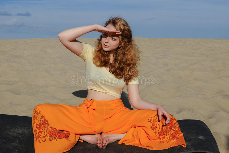 Young redhead woman sitting in purna titli yoga pose on the beach. Young slim redhead woman sitting in purna titli yoga pose on the beach. butterfly pose. on the royalty free stock images