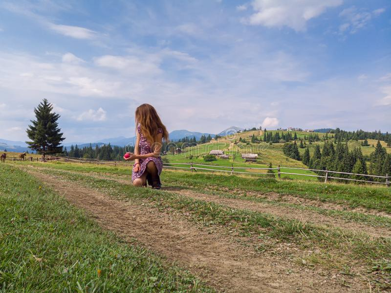 Young redhead woman sitting on a trail through the mountains valley during warm sunny summer day. Looking out over distant grazing horses - healthy lifestyle stock images