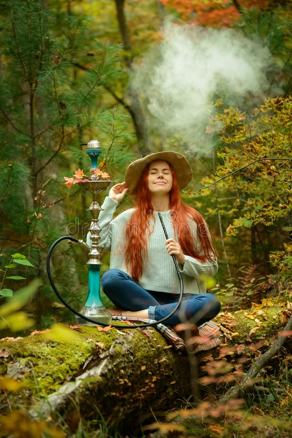 Young redhead woman smoking Hookah in forest. Young redhead woman in hat smoking Hookah in forest stock photos