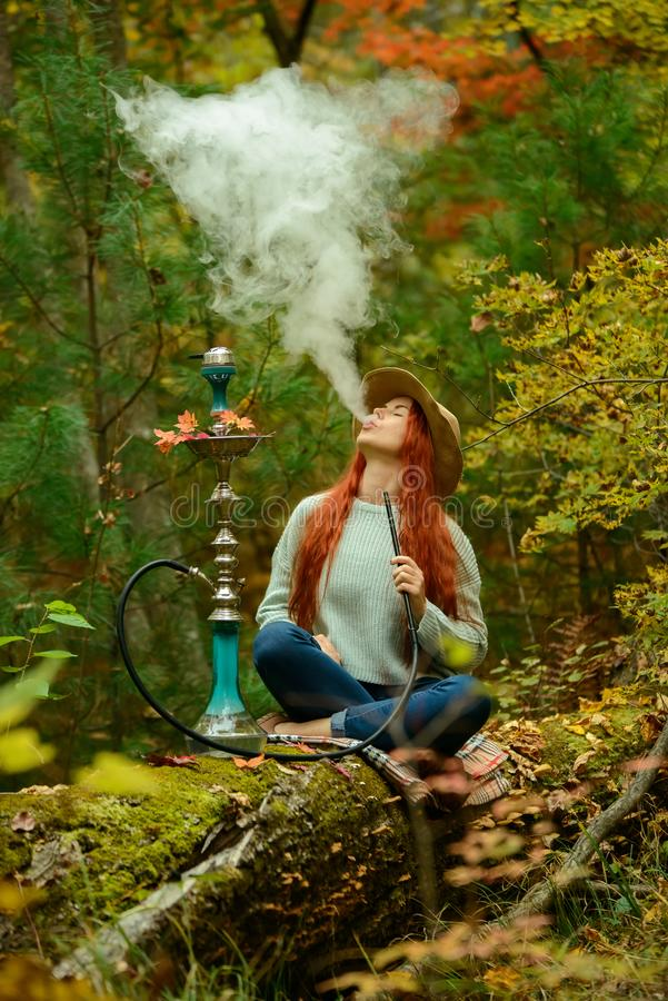 Young redhead woman smoking Hookah in forest. Young redhead woman in hat smoking Hookah in forest stock image