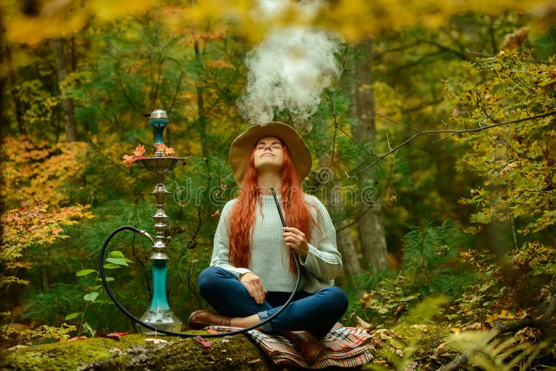 Young redhead woman smoking Hookah in forest. Young redhead woman in hat smoking Hookah in forest royalty free stock images