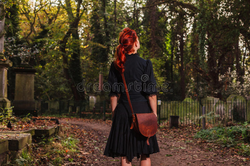 Young redhead woman standing in cemetery royalty free stock images