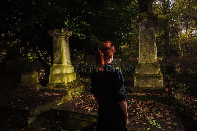 Young redhead woman standing in cemetery stock images