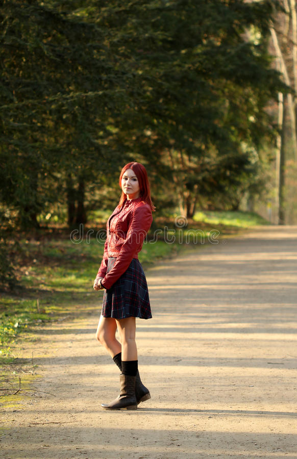 Young redhead woman standing on forest road stock photography