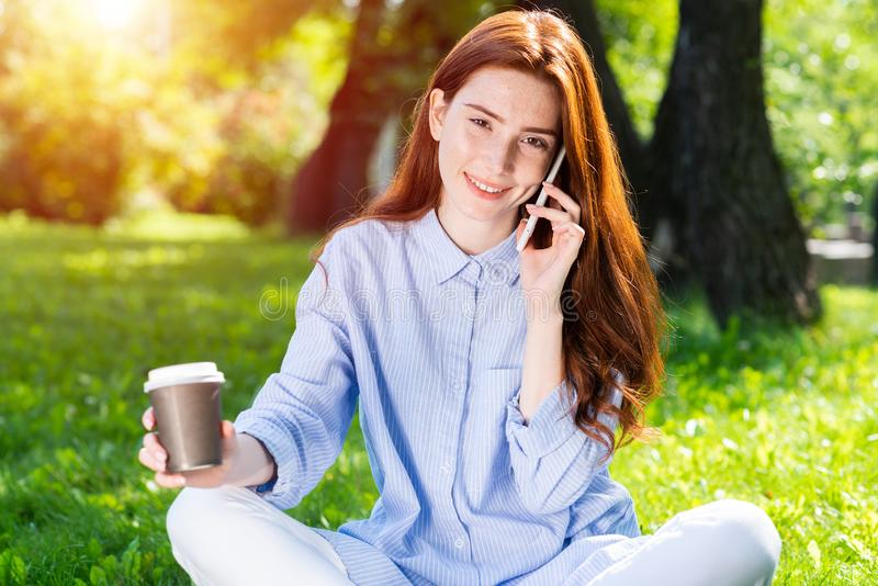 Young redhead woman talking on smartphone stock photography