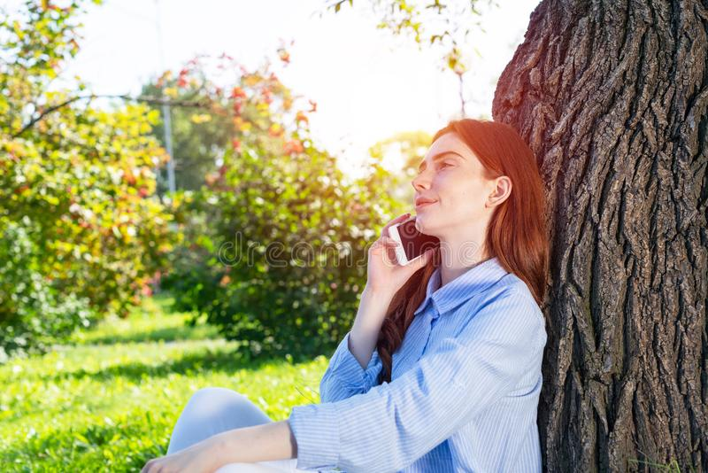 Young redhead woman talking on smartphone royalty free stock images