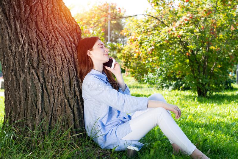 Young redhead woman talking on smartphone stock image