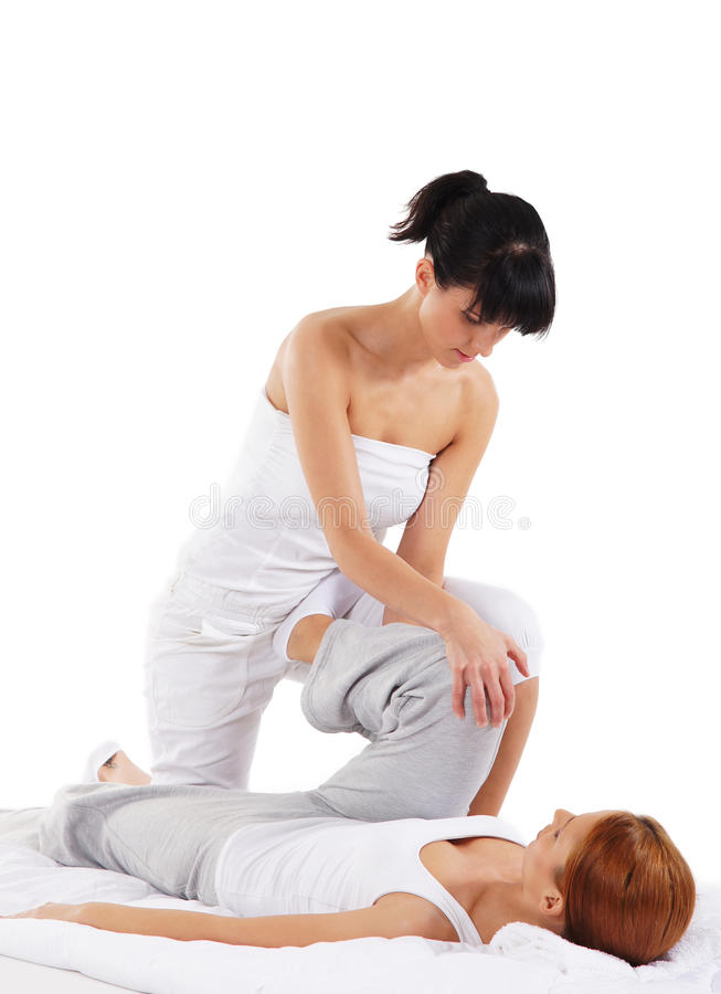 A young redhead woman on a Thai massage. A young and attractive redhead Caucasian women on a Thai massage procedure with female therapist. The image is taken on royalty free stock photo