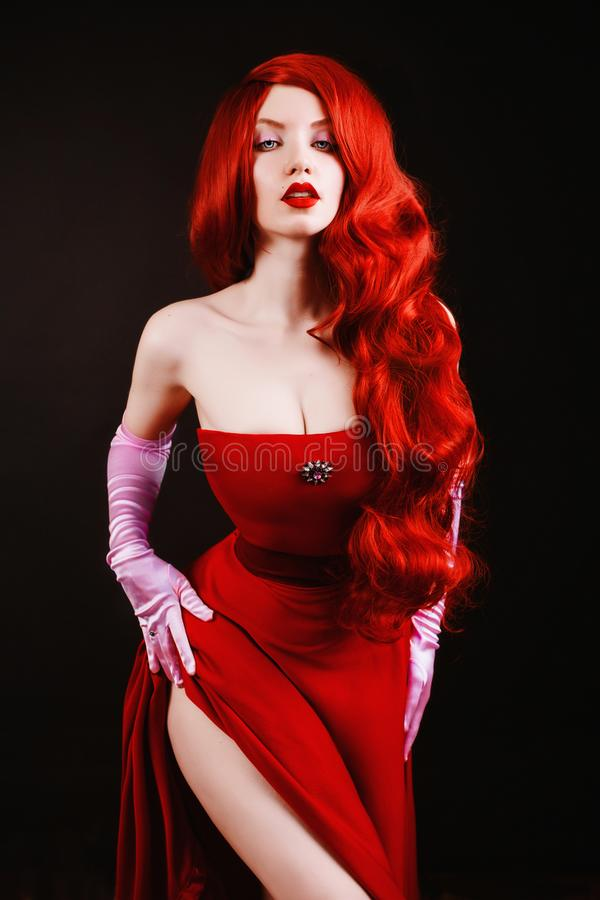 Young redhead woman with very long hair in red gown on a black background. A beautiful girl with pale skin, red lips and blue eyes. Gown on a beautiful slim stock images