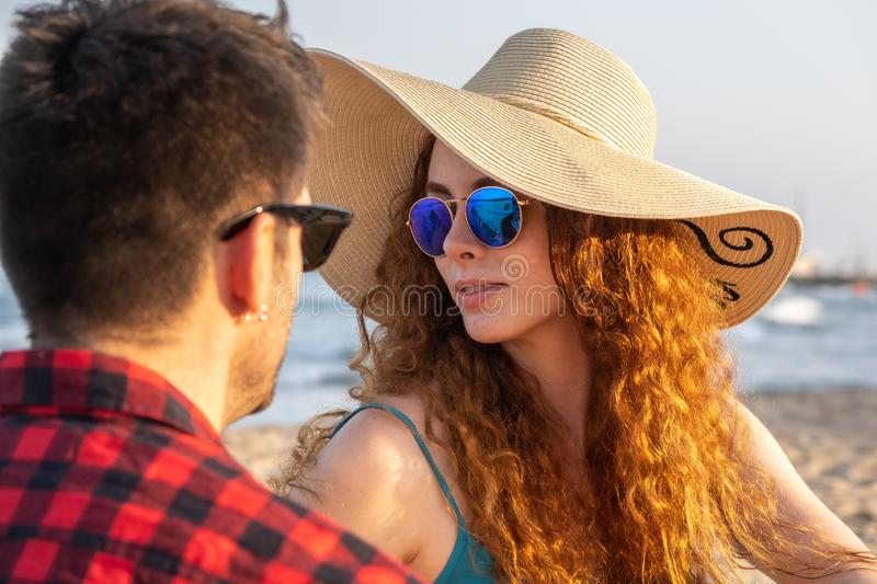 Young redheaded girl with a hat and sunglasses spends the afternoon with a brown boy on a Mediterranean beach. royalty free stock photos