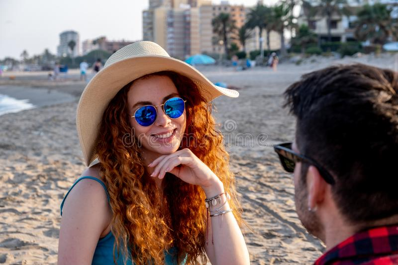 Young redheaded girl with a hat and sunglasses spends the afternoon with a brown boy on a Mediterranean beach. royalty free stock photo