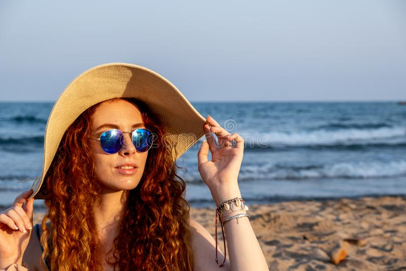Young redheaded girl sits on the shore of a Mediterranean beach stock photos