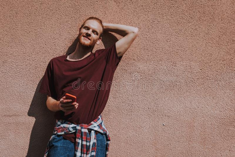 Young relaxed hipster man with mobile phone. Urban lifestyle concept. Waist up portrait of young smiling hipster guy relaxed leaning on building wall with mobile stock photos