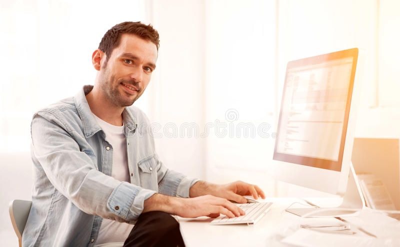 Young relaxed man using tablet at home. View of a Young relaxed man using tablet at home royalty free stock photography