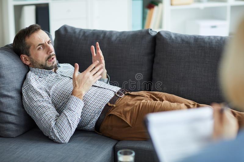 Man explaining problem. Young relaxed men lying on couch while talking to counselor and explaining his trouble during individual session royalty free stock image