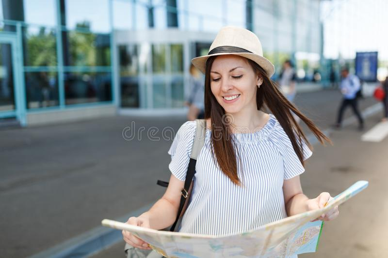 Young relaxed traveler tourist woman in hat, light clothes hold paper map at international airport. Female passenger. Traveling abroad to travel on weekends stock photo