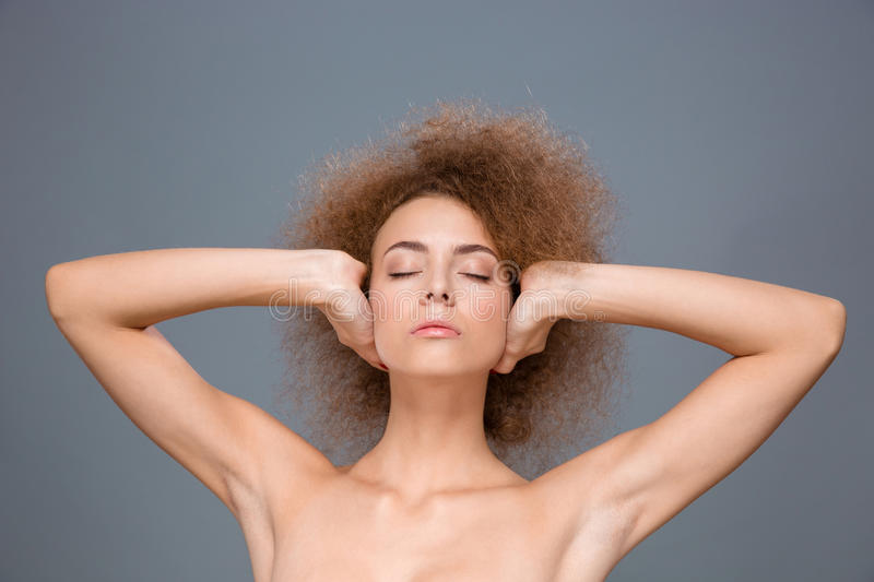 Young relaxed woman with eyes closed covering ears by hands royalty free stock image