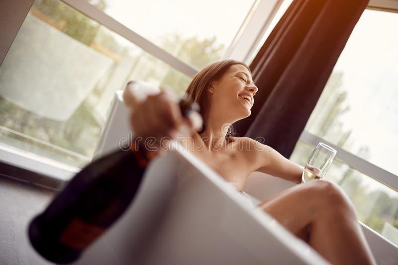 Relaxing girl in bath with foam and drink champagne. Young relaxing girl in bath with foam and drink champagne royalty free stock photography