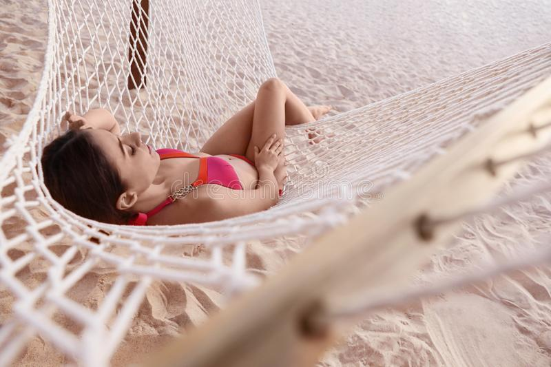 Young  relaxing in hammock on beach. Young woman relaxing in hammock on beach royalty free stock image