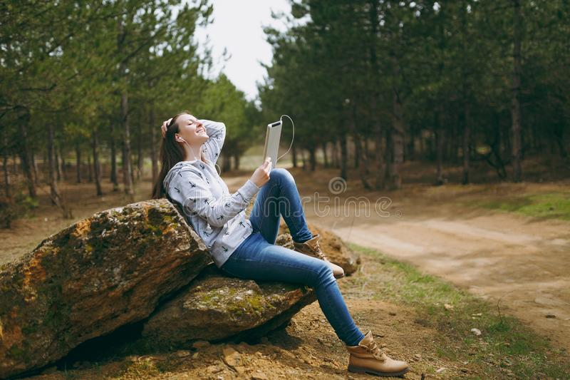Young relaxing smiling beautiful woman in casual clothes with earphones sitting on stone using tablet pc computer in. City park or forest on green background royalty free stock image