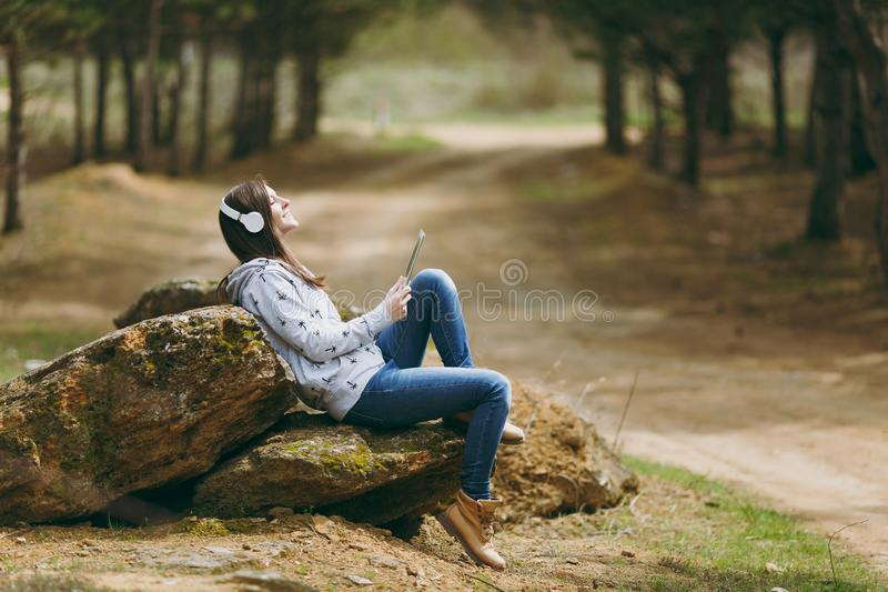 Young relaxing smiling beautiful woman in casual clothes with headphones sitting on stone using tablet pc computer in. City park or forest on green background royalty free stock image