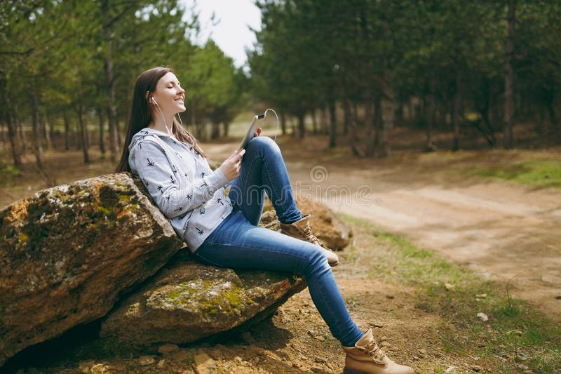 Young relaxing smiling woman in casual clothes sitting on stone listening music with earphones and tablet pc computer in. City park or forest on green stock photos