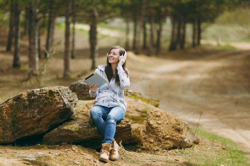 Young relaxing smiling woman in casual clothes sitting on stone listening music with headphones and tablet pc computer. In city park or forest on green stock photos
