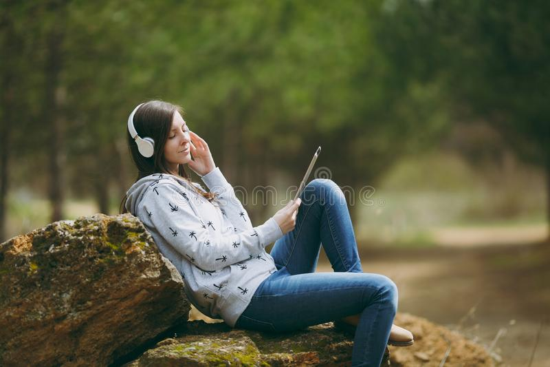 Young relaxing woman in casual clothes sitting on stone listening music with headphones and tablet pc computer in city. Park or forest on green blurred royalty free stock photo