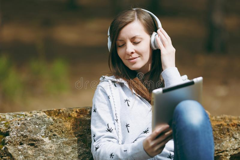 Young relaxing woman in casual clothes sitting on stone listening music with headphones and tablet pc computer in city. Park or forest on green blurred royalty free stock photography