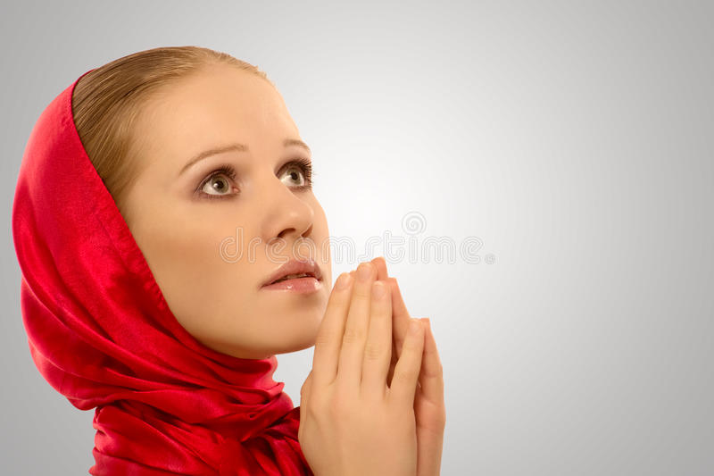 Young religious woman in a red shawl prays