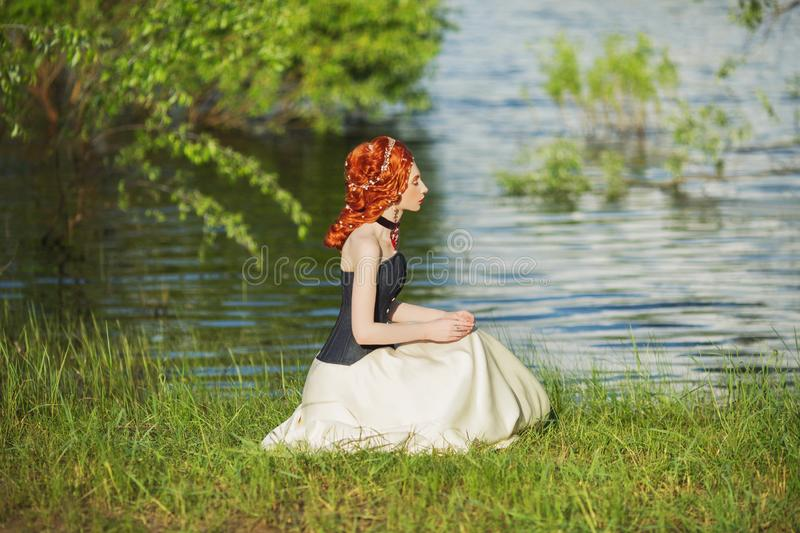 Young renaissance princess with hairstyle sit on nature background. Rococo queen in white historic dress against backdrop of blue. Water. Princess in corset stock image